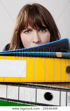 Exhausted business woman in the office with a pile of folders at front