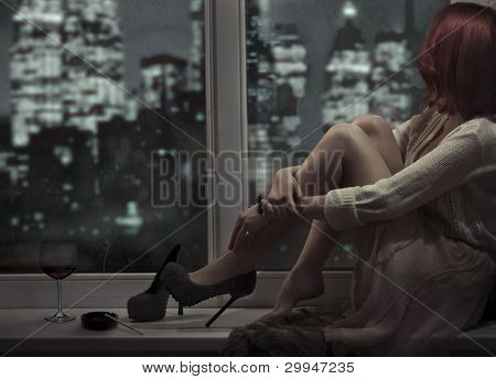 Alone beautiful woman sitting on window and looking on night city