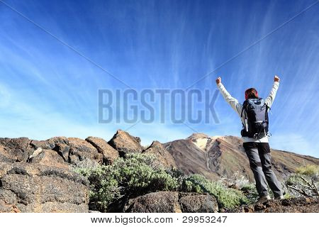 Hiker cheering. Happy hiking woman with arms raised overcoming challenges. From hike on volcano Teide, Tenerife, Canary Islands, Spain.