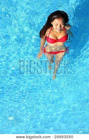 Woman relaxing in swimming pool. Beautiful gorgeous young bikini model bathing in blue swimming pool on resort during holiday. Pretty multiracial Asian / Caucasian woman in red bikini.