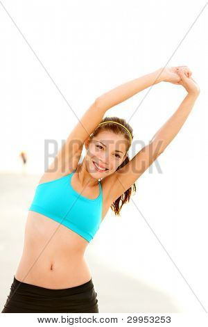 Workout woman training on beach. Fit fitness model stretching after running outside. Beautiful young mixed race Asian Caucasian female fitness model smiling happy.