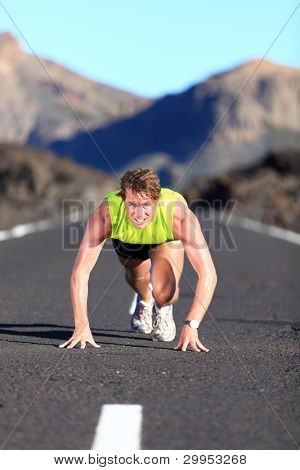 Sprinter ready for sprint. Man runner starting running sprint on road in beautiful mountain nature landscape. Fit Caucasian male fitness model during work out.