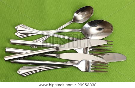 Forks, spoons and knives on a green tablecloth