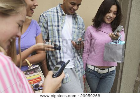 Young people examining cell phones