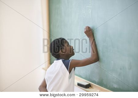 Young boy writing on chalkboard