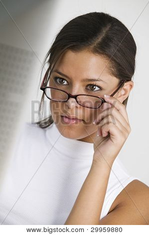 Young woman looking over glasses