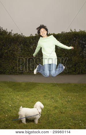 Young woman jumping for joy while dog watches