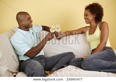 Couple on couch toasting with white wine