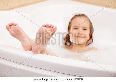 Kind in der Badewanne. Mädchen wäscht im Badezimmer. Fokus auf Fuß