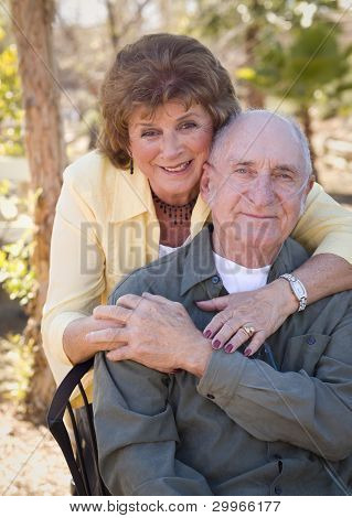 Senior Woman Outside with Seated Man Wearing Oxygen Tubes.