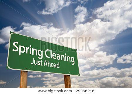 Primavera limpeza sinal de estrada apenas à frente de verde com nuvens dramáticas, raios de sol e céu.