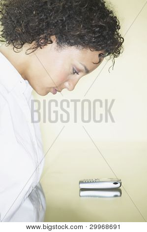 Profile of woman staring at cell phone