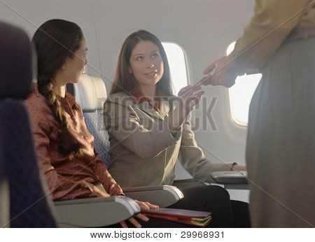Young woman passing note to male passenger
