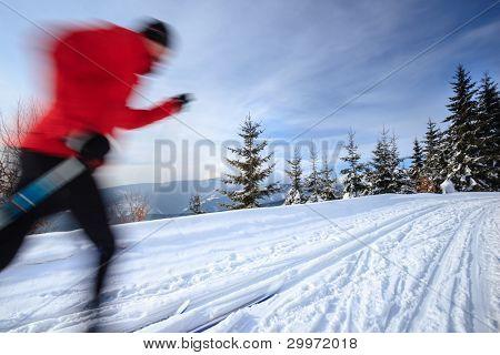 Esquí: esquí de fondo de la joven en un día de invierno soleado precioso (motion blur techn