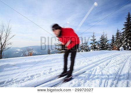 Cross-country skiing: young man cross-country skiing on a lovely sunny winter day (motion blur technique is used to convey movement)