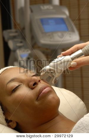Young afro american woman getting ultrasonic and laser face treatment at beauty spa.