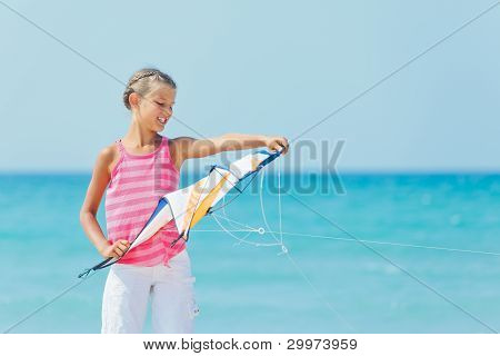 Cute girl on beach playing with a colorful kite