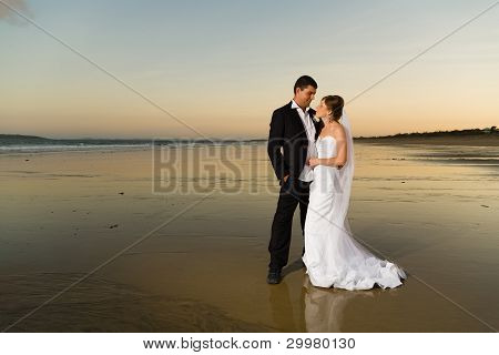 Newlyweds On A Deserted Beach At Sunset