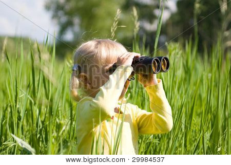 The little girl is looking through binoculars