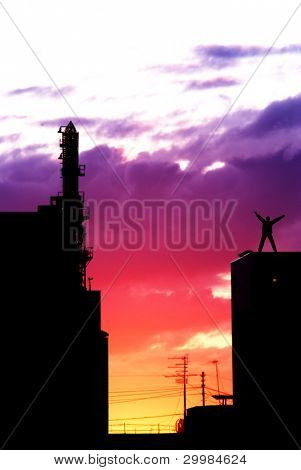 Man standing on the edge of building on sunrise