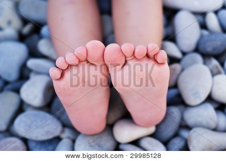 Children's feet on the beach with gravel
