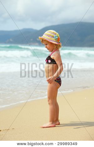 Beautiful little girl on the beach by the sea