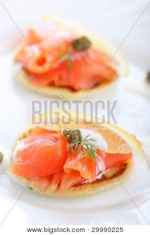 delicioso aperitivo con crepes de salmón, crema fresca de limón y alcaparras