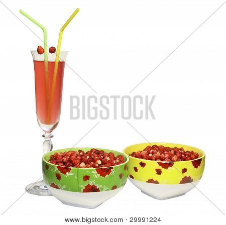 Two round plates with berries of wild strawberry and a glass of juice