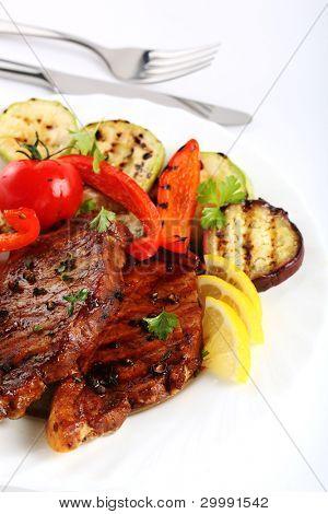 Steak vom Grill Fleisch mit Gemüse auf weißem Hintergrund