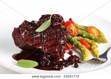 Steak Sauce mit Wein und Zwiebeln, serviert mit Spargel auf einem weißen Teller