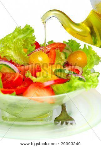 Ensalada de verdura con aceite de oliva verter de botella en fondo blanco aislado