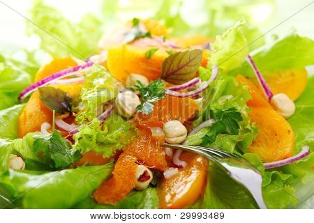 Fresh salad mix with persimmons, mandarine orange and hazelnuts
