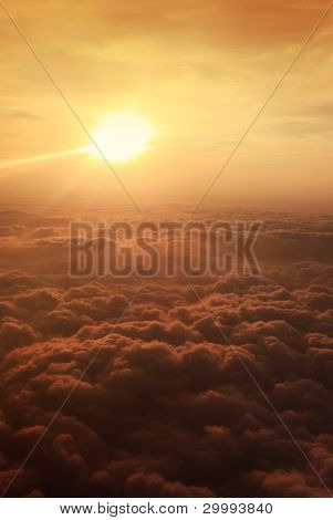 View of sunset above clouds from airplane window