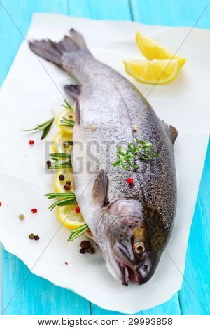 Fresh fish with lemon, rosemary and peppercorn.(Rainbow trout)