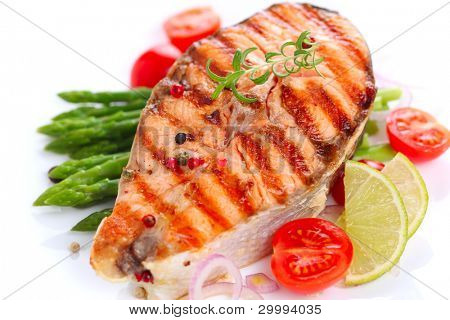 grilled salmon with lime, asparagus and cherry tomatoes on white plate