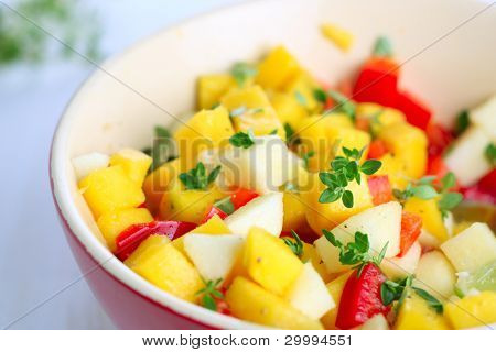 Fresh salad with mango, red pepper, apple and lemon thyme