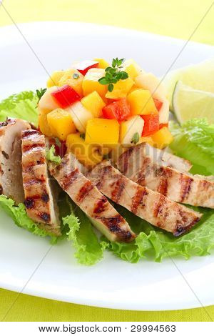 Grilled chicken breast with fresh mango salsa on white plate