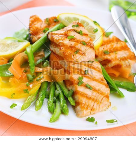 grilled salmon with asparagus on white plate, soft focus