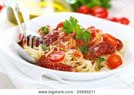 Spaghetti with tomato sauce, sun dried tomato and shrimps on white plate