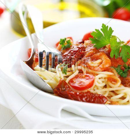 Spaghetti mit Sonne getrockneten Tomaten und Tomatensauce auf weißem Teller