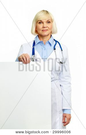 Positive female doctor holding a poster isolated on white background
