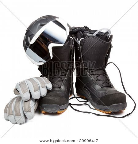 Snowboard boots with helmet gloves and goggles on white background