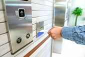 Securing Lift Or Elevator Access Control, Mans Hand Is Holding A Key Card Lay Up To Insert In Card  poster