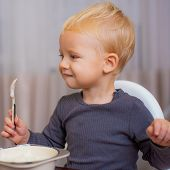 Boy Cute Baby Eating Breakfast. Baby Nutrition. Eat Healthy. Toddler Having Snack At Home. Child Eat poster