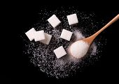 Sugar Scattered From Wooden Spoons On A Black Background. Sugar Wave. Sugar Sand And Sugar Cubes Pou poster