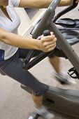 stock photo of exercise bike  - Perspective shot of a young woman on excercise bike in the gym