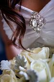 pic of brooch  - Detail of brooch on a wedding dress with a lock of hair and the bouquet in shot - JPG