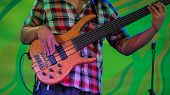 Close Up Shot - Male Bassist Hands Playing Bass Guitar On Stage Of Ethnic Open Air Concert. Entertai poster