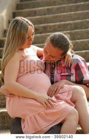 Portrait of a happy young man looks at his pregnant wife belly . outdoor .