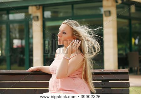 Beautiful blond pregnant woman relaxing on the bench . outdoor.